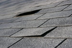 A close-up image of a damaged asphalt shingle roof with shingles that are coming loose.